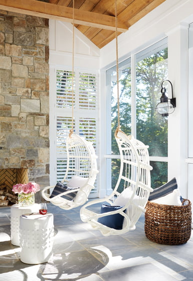 Serena & Lily hanging chairs offer perches for fireside chats on the screened porch.