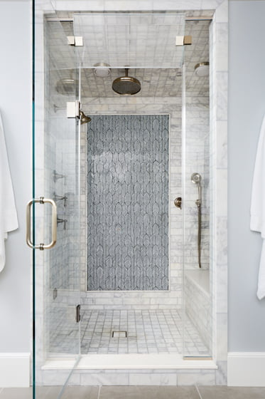 A marble-clad shower in the master bath boasts mixed tiles from Architectural Ceramics.