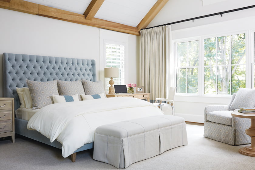 In the vaulted master bedroom, the bed is adorned with a custom headboard crafted in Kravet linen.
