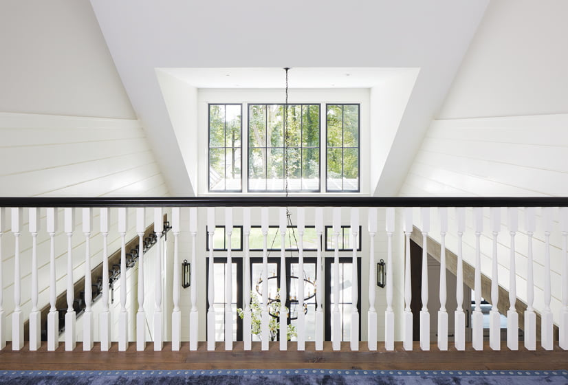 A two-story, vaulted ceiling creates a hub connecting the communal area to the spaces below.