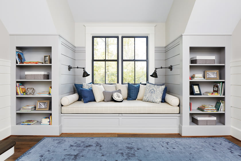 Built-ins flank a window-seat reading nook in the second-floor gathering place.