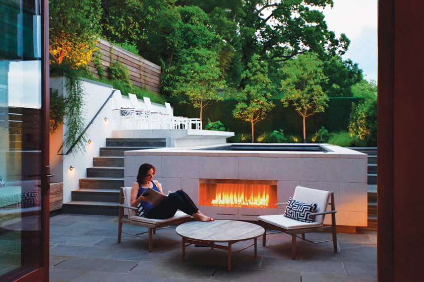 Project architect Colleen Gove Healey relaxes by the gas fireplace, set into the swimming-pool wall.
