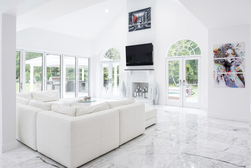 The living room showcases marble floors, a ZGallerie sectional and bold, graphic art.