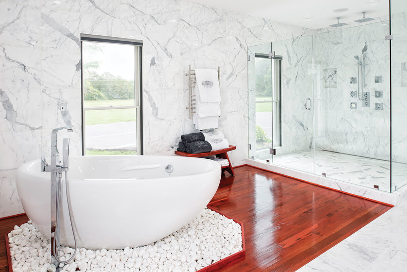 The luxurious master bath features a teak floor and a soaking tub on a bed of Caribbean beach pebbles.