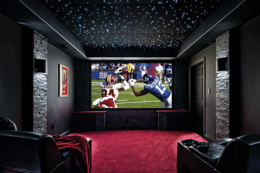 A home theater designed by Norman is decorated with a ceiling resembling a starry sky.