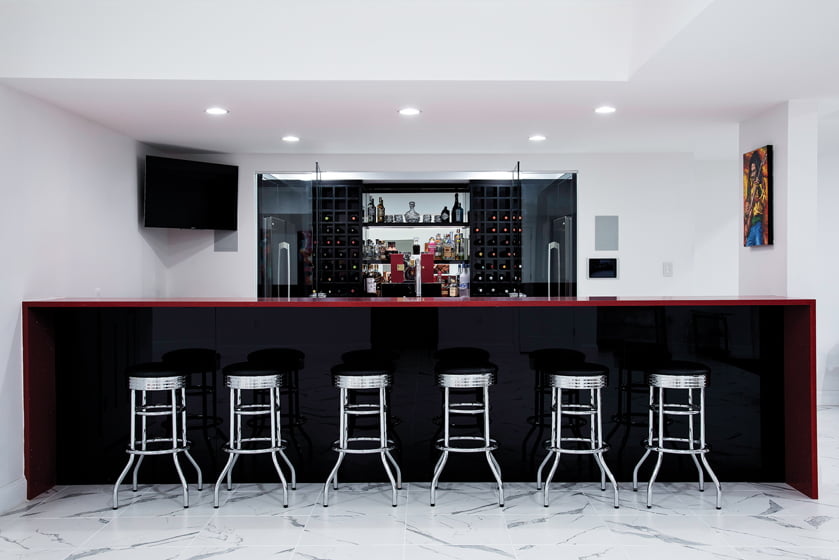 In the lower-level rec room, a bar topped by red quartz boasts a wine cellar and full bar.