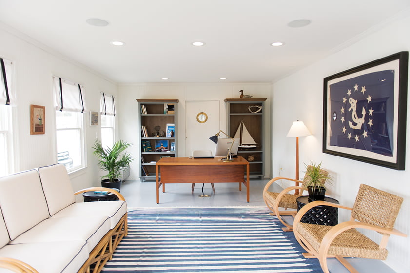 The reception area is light and airy, with a white-painted floor, blue-and-white-striped rug and rattan seating.