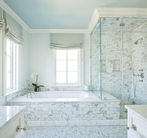 The master bath, clad in marble, boasts a tub and shower enclosure designed as one unit. © Gordon Beall