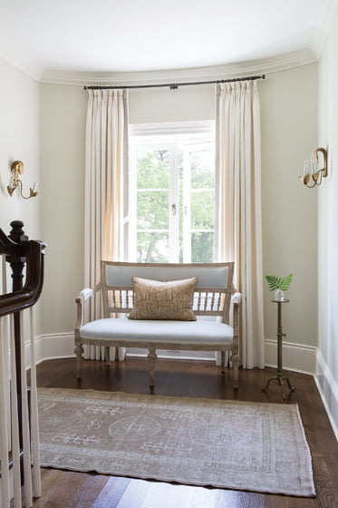 A bench from Tone on Tone and side sconces from Marston Luce adorn the second-floor landing.