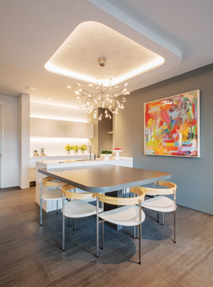 A painting by Michael Hedges overlooks the custom dining table, which is integrated into the kitchen peninsula to conserve space.