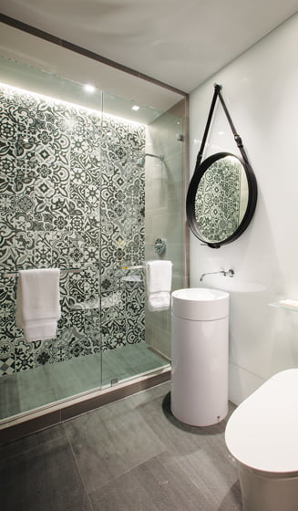Accent wall tiles from Porcelanosa make a statement in the guest  bathroom.