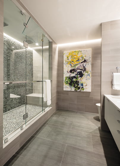 The condo's stone flooring is carried onto the walls in the master bath; the shower wall is covered in pebbled tile from Porcelanosa.