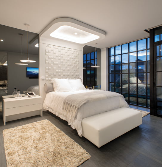 In the master bedroom, padded, faux-leather wall tiles frame a custom bed designed by FORMA.