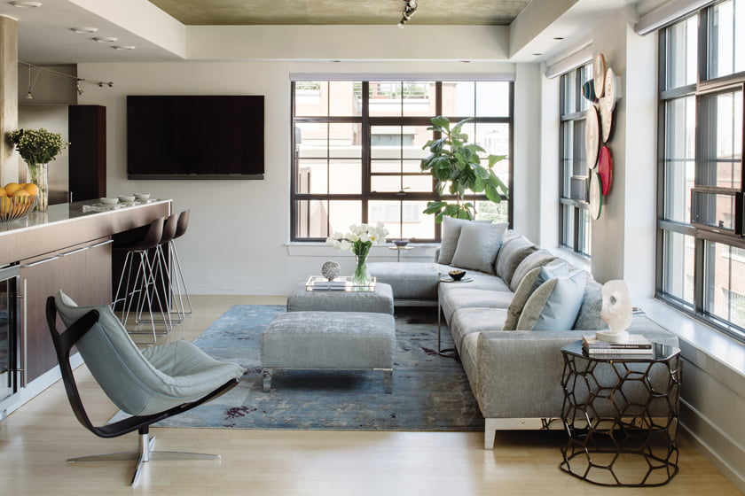 On one side of the L-shaped space, a rug from Doris Leslie Blau anchors seating from Roche Bobois.