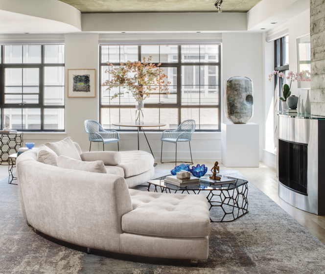 The living room boasts a gracefully curved Della Robbia sectional from Theodores atop a C.G. & Coe rug.