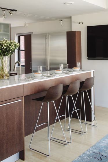 The existing kitchen combines dark-wood cabinetry, marble countertops and stools from Contemporaria.