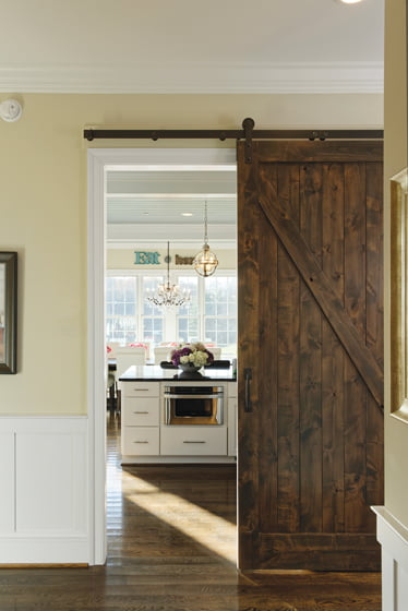 A barn door leads into the open dining room and kitchen.