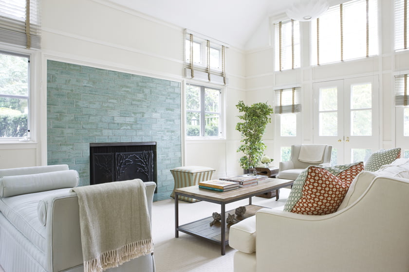 Muted indoor-outdoor textiles and a wool rug temper the family room's splashy aqua fireplace surround.
