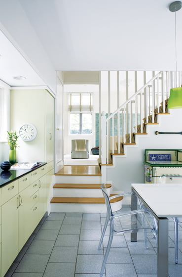 Part of a previous addition, the sunny kitchen features pale lime-green cabinets.
