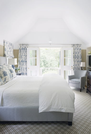 A refuge with its own balcony in the trees, the master bedroom boasts a custom headboard of Meyer's design.