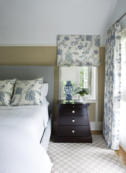 Throw pillows, a Roman shade and drapes in a blue-and-white Kravet floral animate the calm, neutral space.