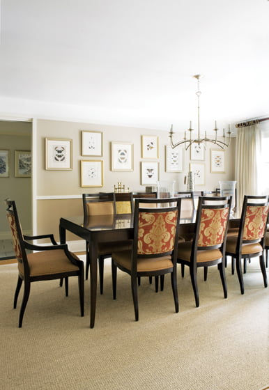 The dining room is dressed up with chair backs in red-and-gold damask and a Currey & Company chandelier.