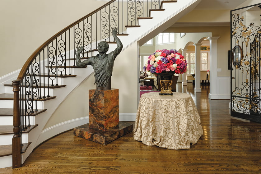 A bust of maestro Julius Rudel abuts the foyer's sweeping staircase; iron gates open to the music room,