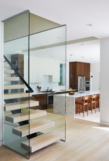 A modern staircase with open risers occupies the space between the old and new parts of the house.