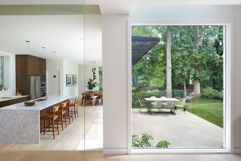 Floor-to-ceiling glass opens to backyard views; the kitchen centers on a marble-topped island and incorporates a dining area.