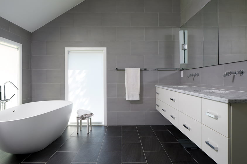 The master bathroom boasts double sinks on a floating vanity and large-format porcelain tiles on the floors and walls.