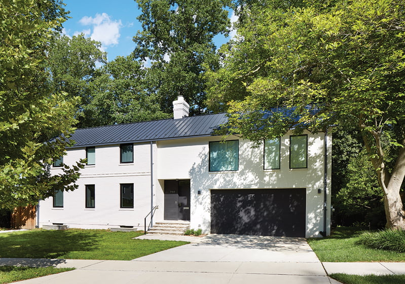 As seen from the street, the house now extends to include a brick-clad addition containing a garage and the master suite.