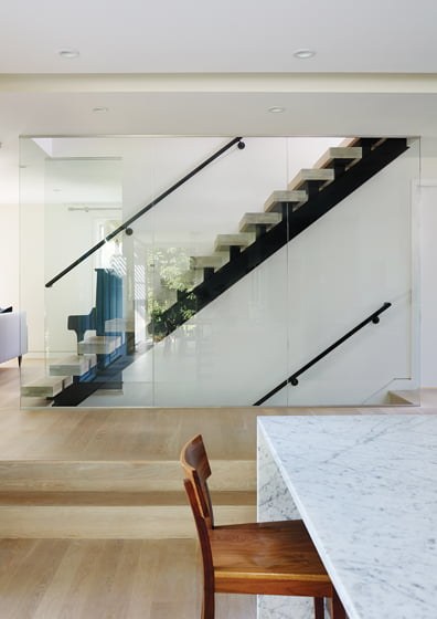 A panel of glass next to the stairs ensures safety while allowing for light.