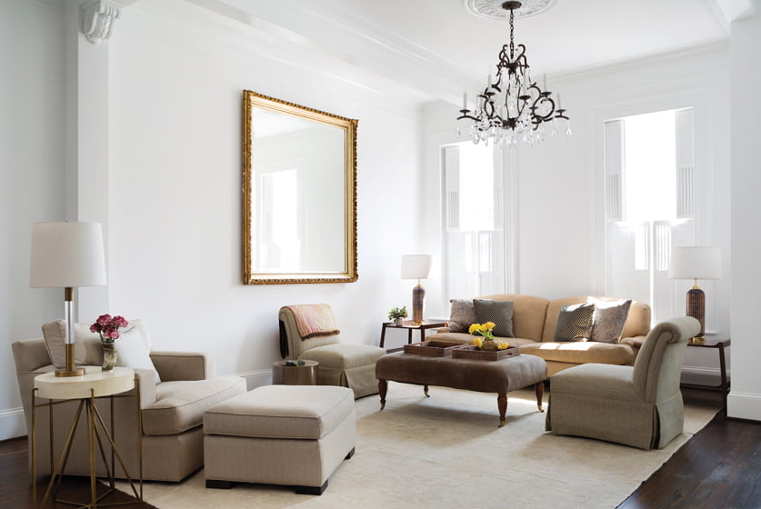 The spacious living room contains two seating areas crowned by matching crystal-and-iron chandeliers.