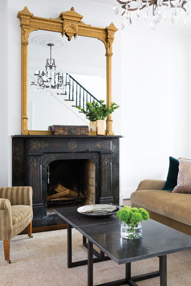The living room's second furniture grouping clusters around the fireplace.
