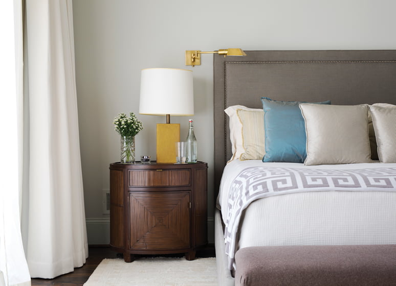 The master suite features a Restoration Hardware bedstead and commodes by McGuire doubling as nightstands.
