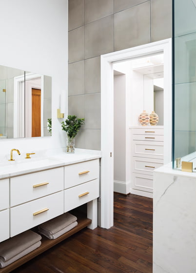 The master bath, accessed via a  walk-in closet, combines a custom, marble-topped vanity and concrete-look porcelain wall tile.