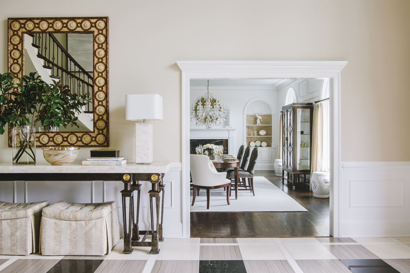A Maitland-Smith console and mirror grace the foyer, which opens to the dining room.