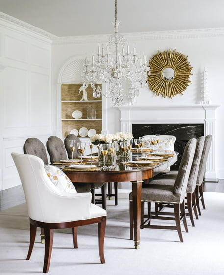 Armless Lillian August chairs in a Wesley Hall fabric pull up to an oval dining table.