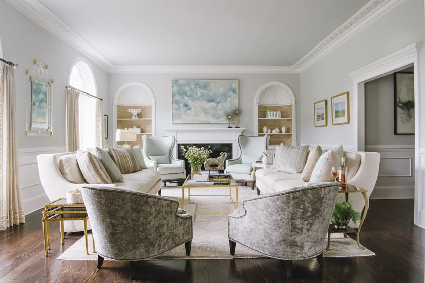 In the living room, art above the mantel and over a Lillian August chest inspired pale aqua tones in the textiles.
