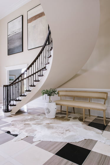 The foyer's stone floor in a strong plaid pattern establishes the home's color palette.