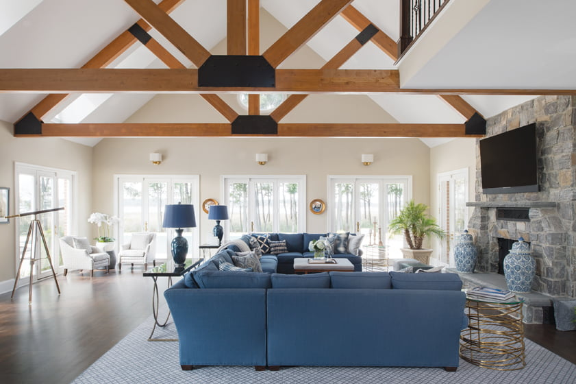 The rec room boasts a vaulted, beamed ceiling above a pair of large sectionals upholstered in hardy Crypton.