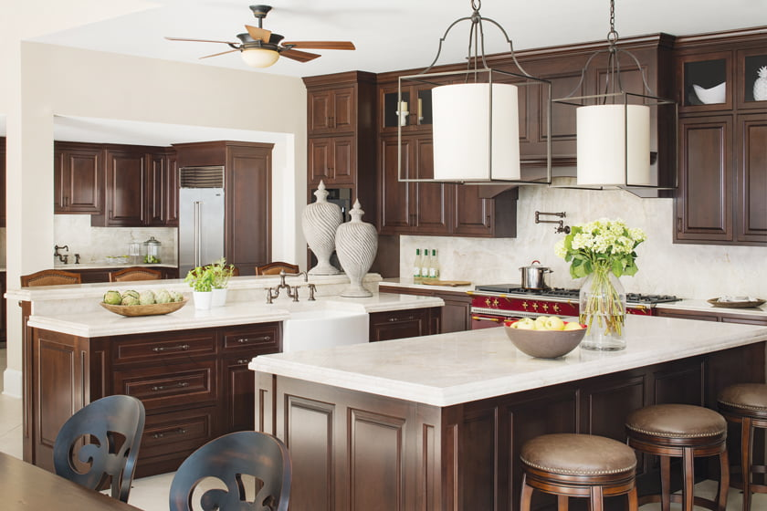 Cherry cabinetry is topped by quartzite counters with ogee detailing. A red Lacanche stove adds a pop of color.