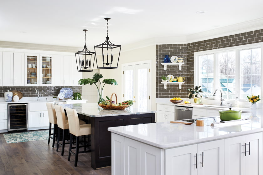 The open kitchen is structured around a granite-topped island and a peninsula housing the cooktop.