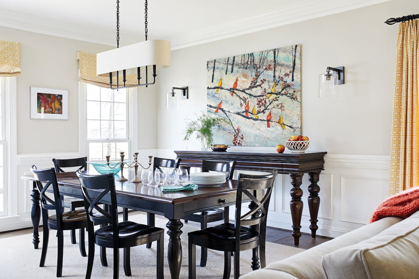 The dining room combines traditional, dark-stained furniture with industrial-style lighting and art by Keith Patterson.