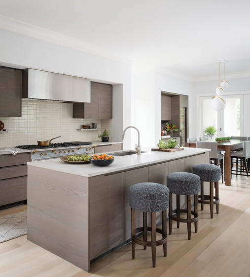 The kitchen boasts a Lacanche chef's range, Poliform cabinets and honed rhodonite countertops.