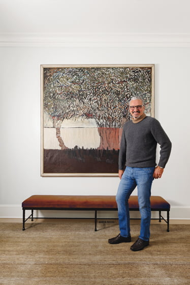 Paolo Sacco poses near a work by Georgetown artist Dale Loy in the foyer. Portrait: Bob Narod.