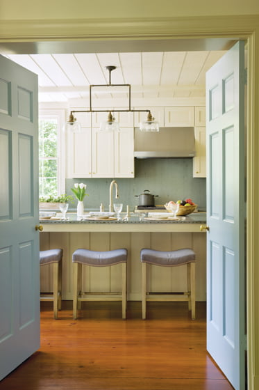 In the kitchen, wide bead-board detailing conveys farmhouse style.