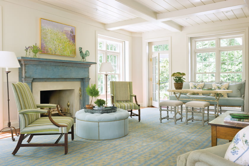 The family room captures sweeping outdoor views. A Wolf Kahn painting above the mantel depicts a pastoral landscape.