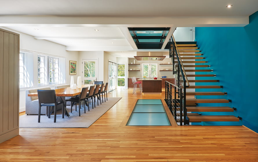 In the addition, a dining table was made using logs recycled from the house. Glass floor panels admit light to the basement.