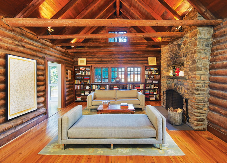 The exposed timbers and stone fireplace in the living room were preserved to maintain a rustic, log-cabin look.